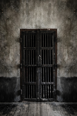 locked up in a cage: Rusted iron bars door on old wall, vintage style add vignette.  Add light smoke looking soft focus.
