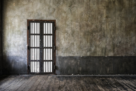 incarceration: Rusted iron bars door on old wall, main light from left side, vintage style add vignette.