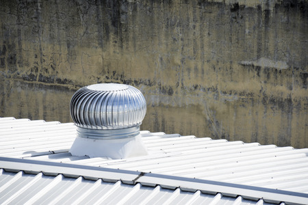 Stainless steel exhaust fan on factory roof.