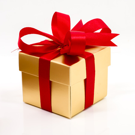 gift background: Beautiful gold present box with red bow and ribbons on white backgound