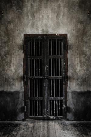 rejas de hierro: Rusted puerta de barrotes de hierro en la pared vieja, estilo vintage añadir viñeta. Añadir humo looking luz de enfoque suave.