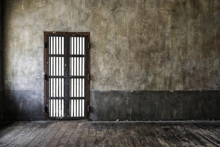 puertas de madera: Rusted puerta de barrotes de hierro en la pared vieja, luz principal del lado izquierdo, estilo vintage añadir viñeta. Foto de archivo