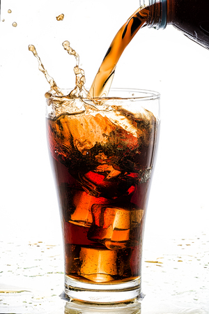 Pouring cola into glass with ice cubes, on white background
