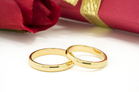 Wedding rings and artificial rose on white background, horizontally Selective focus