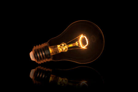 metal filament: Bright Light Bulb on black background Stock Photo