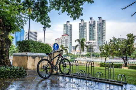 rack: Bicycle parking rack in public park with modern building on background.