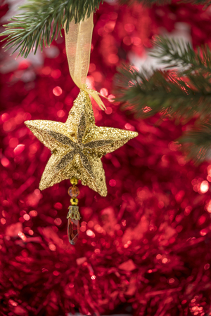 star ornament: Christmas star ornament hang on Christmas tree branch with red bokeh background