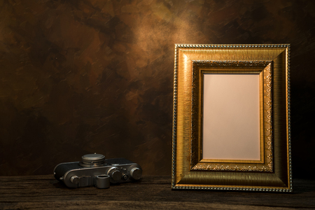 recollections: Still life of picture frame on table with vintage camera. Stock Photo