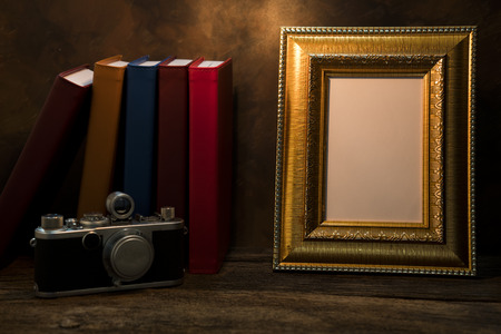 recollections: Still life of picture frame on table with vintage camera and diary book.