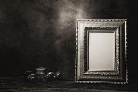 recollections: Still life of picture frame on table with vintage camera, Black and White image Stock Photo