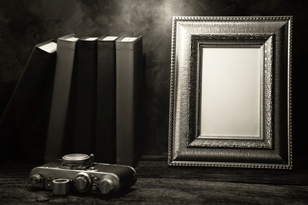 recollections: Still life of picture frame on table with vintage camera and diary book, Black and White image Stock Photo