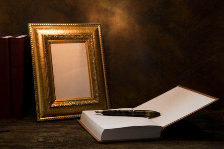 picture book: still life of picture frame on table with diary book.