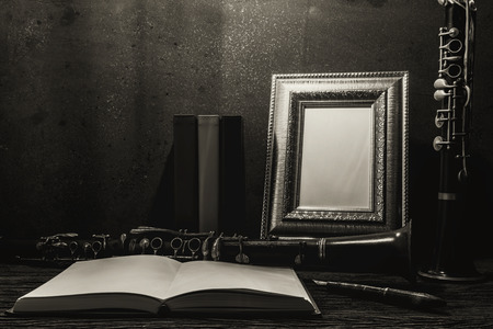 Still life of picture frame on wooden table with clarinet, black and white image