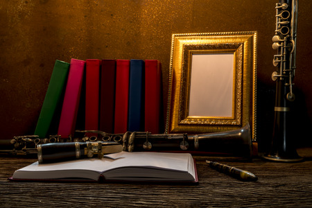 antique table: Still life of picture frame on wooden table with clarinet.