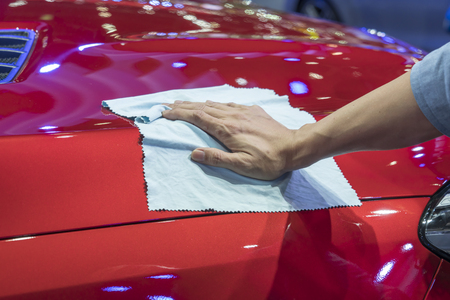 microfiber: Hand with microfiber cloth cleaning car.