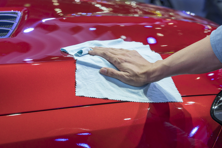 polish: Hand with microfiber cloth cleaning car.