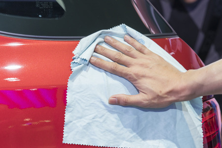 microfiber cloth: Hand with microfiber cloth cleaning car.