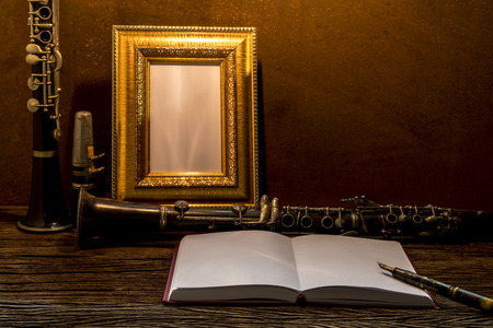 clarinet: Still life of picture frame on wooden table with clarinet.