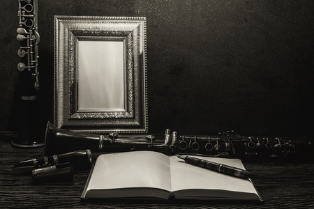 clarinete: Still life of picture frame on wooden table with clarinet.