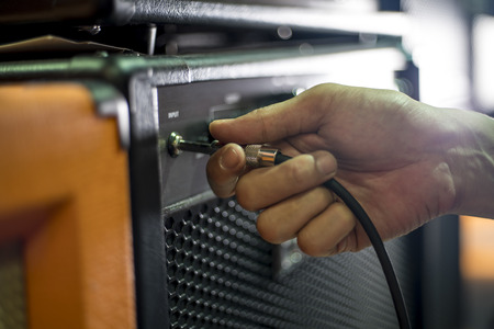 guitar amplifier: Closed up hand holding jack plug-in to the guitar amplifier, shallow DOF, selected focus
