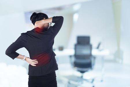 Femme d'affaires avec des maux de dos, le modèle est femme asiatique.
