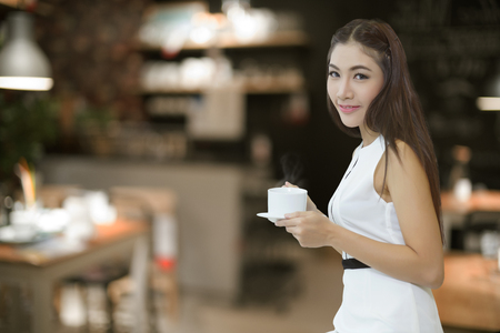 Beautiful Asian business woman holding coffee cup with coffee shop on background photo