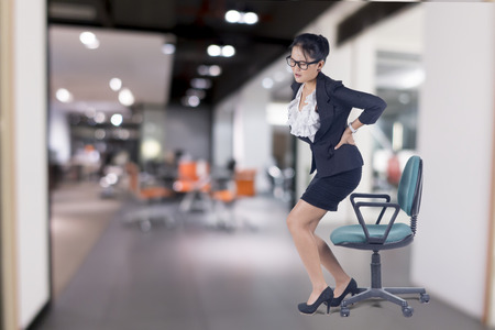 massage chair: Business woman with backache after long work on chair, Model is Asian woman. Stock Photo