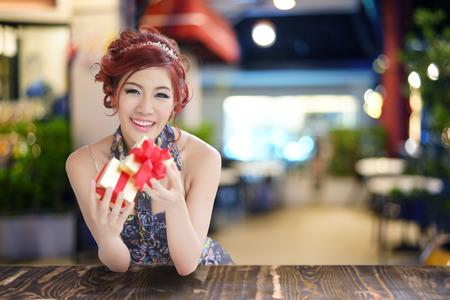 Beautiful young woman opening gift box, photo