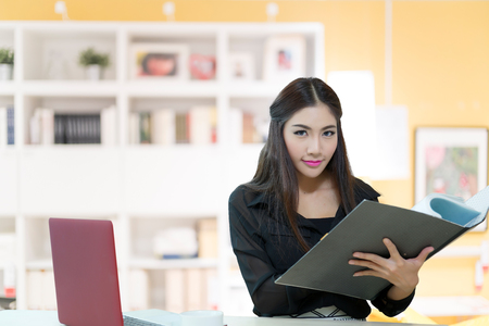 Pretty business lady working at desk, Model is Asian woman. photo