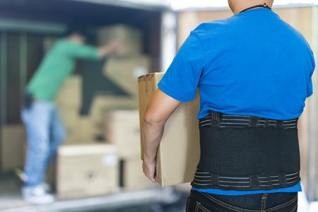 El hombre levantar pesado del cartón uso del cinturón de soporte para proteger la espalda, fondo borroso de cajas de cartón de elevación de los trabajadores Foto de archivo