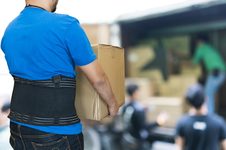 back injury: Man lift heavy carton wearing support belt for protect his back, blurred background of worker lift cartons Stock Photo