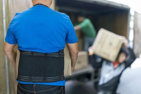 De mens heft zwaar karton op dragend steunriem voor beschermt zijn achter, vage achtergrond van de dozen van de arbeiderslift