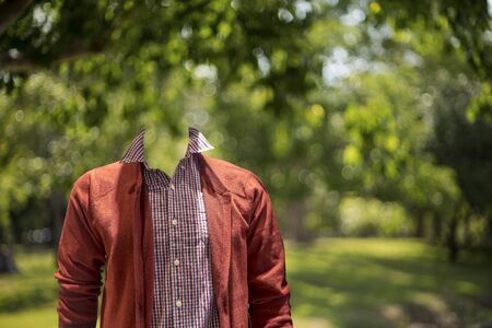 without clothes: Man wearing casual without head with bokeh leaf background.