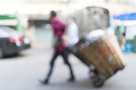 pushes: Blurred image of worker pushes the cart with products down on street for background use.