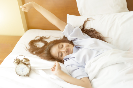 Young Asian woman in bed trying to wake up with alarm clock.