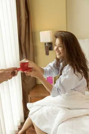 awaking: Husband serves coffee in bed to his wife and awaking her. focus at coffe cup Stock Photo