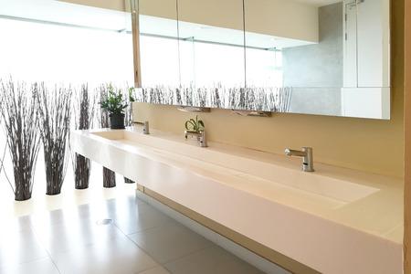 Row of hand washing sinks in modern public toilet.