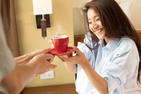 awaking: Husband serves coffee in bed to his wife and awaking her. focus a woman