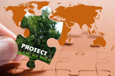 warming up: Close up of jigsaw puzzle with protection tree, Global Warming concept
