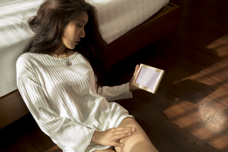 Beautiful women in the bedroom in the morning, looking at pictures in her hand, a sense of loneliness, nostalgia, or love.