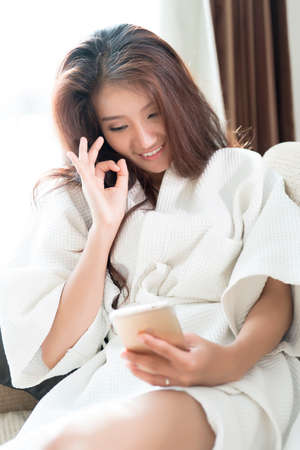 vdo: Happy woman presenting OK sign while video call with her smartphone. Stock Photo