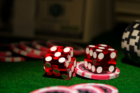 Red dices on chip and dollar bills, casino concept.