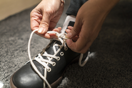 shoelace: close up two hands are pulling the knot of leather shoes for take off shoes. Stock Photo