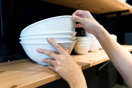 Selective focus at woman hands picking up the white big bowl, stacked on the wooden shelf in the kitchen.