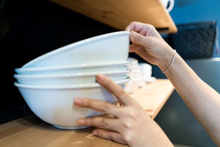 hand picking up the top of white bowl, stacked on the shelf in the kitchen. Stock Photo