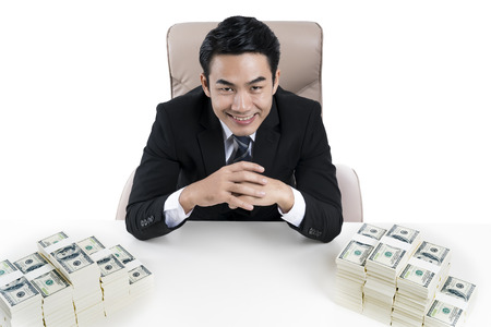 A young businessman smiling and the pile large amounts of money on desk, on white background, concept of business, financial and money laudering. Stock Photo