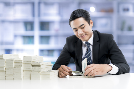 젊은 은행원 웃 고 지폐 및 은행 사무실 배경, 개념 사업 및 금융에 흰색 테이블에 돈의 큰 더미를 세 고있다.