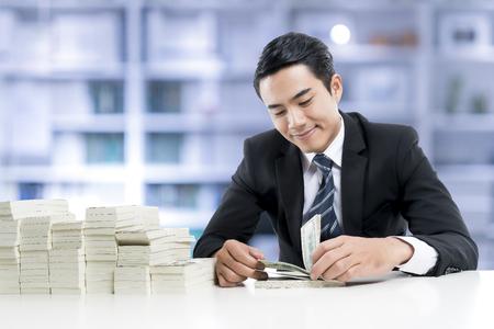 El joven banquero está sonriendo y contando billetes y un gran montón de dinero en la mesa blanca en el fondo de la oficina bancaria, el concepto de negocio y financiero. Foto de archivo - 75634584