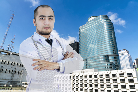 double cross: Double exposure to young smart doctor standing arms crossed in uniform with abstract hospital building  Stock Photo