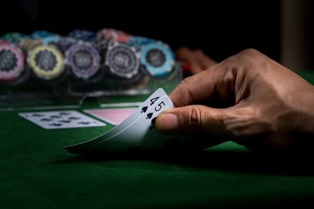 카드를 들고 손을 얼굴 값 9 녹색 테이블에 블랙 잭 게임을 승리 카지노에서 모호한 스택 칩 배경을 보여줍니다 스톡 콘텐츠
